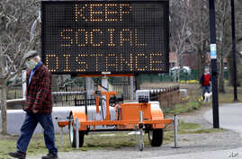 A passer-by wears a mask out of concern for the coronavirus while walking past a public service sign, Tuesday, April 7, 2020,…