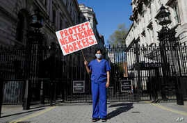 Doctor Meenal Viz holds a banner as she protests outside Downing Street in London, as the country is in lockdown to help curb…