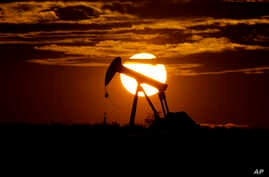The sun sets behind an idle pump jack near Karnes City, Texas, Wednesday, April 8, 2020. Demand for oil continues to fall due…