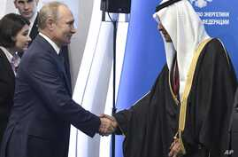 Russian President Vladimir Putin, left, shakes hands with Saudi Arabia's Energy Minister Abdulaziz bin Salman on the sidelines…