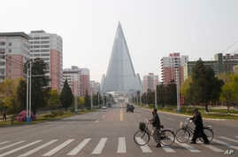 People wearing face masks cross a road in front of the Ryugyong Hotel in Pyongyang, North Korea Tuesday, April 28, 2020. (AP…