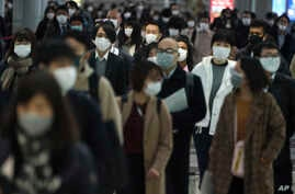 A station passageway is crowded with face mask wearing commuters during a rush hour Monday, April 20, 2020, in Tokyo. Japan's…