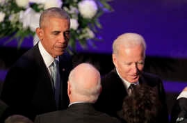 Former President Barack Obama, left, and former Vice President Joe Biden, right, are greeted as they arrive for funeral…