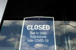 In this Wednesday, April 22, 2020 photo a closed sign is posted in the window of a store because of the coronavirus, in an…
