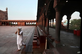 An Indian Muslim wipes his face after performing ablution before prayer on the first day of the holy fasting month of Ramadan…