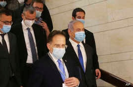 Israeli Prime Minister Benjamin Netanyahu, second right, wears a protective face mask, as he makes his way to attend the…