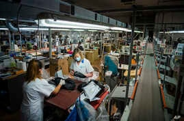 Workers of the Calzaturificio M.G.T shoe factory in Castelnuovo Vomano, central Italy, return to work, Monday, May 4, 2020…