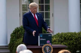 President Donald Trump reaches for a box containing a 5-minute test for COVID-19 from Abbott Laboratories, in the Rose Garden…