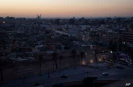 In this Feb. 29, 2020 photo, the walls surrounding the Old City are illuminated before sunrise in Tripoli, Libya. The country…