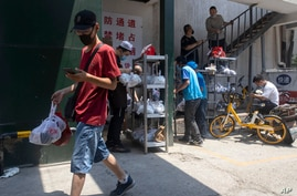 Deliverymen wearing face masks to curb the spread of the coronavirus collect good orders in Beijing on Friday, June 19, 2020…