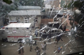 Afghan security security officers are seen through the shattered window of a maternity hospital after gunmen attacked, in Kabul…