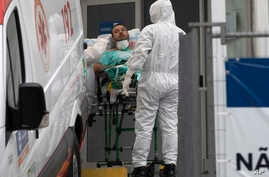 A patient with symptoms related to COVID-19 is brought to a field hospital by workers in full protective gear in Leblon, Rio de…