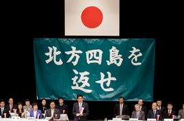 Japanese Prime Minister Shinzo Abe, center, delivers his speech during a national rally marking the Northern Territories Day,…