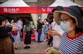 FILE - In this Saturday, June 6, 2020, photo, people wearing face masks to protect against the new coronavirus browse merchant…