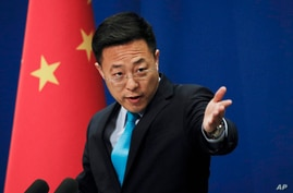 FILE - In this file photo taken Monday, Feb. 24, 2020, Chinese Foreign Ministry new spokesman Zhao Lijian gestures as he speaks…
