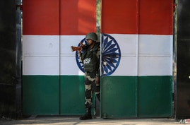 An Indian Border Security Force soldier walks through a gate painted with the Indian flag at the India-Pakistan border at…