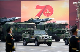 Chinese military vehicles carrying DF-17 ballistic missiles roll during a parade to commemorate the 70th anniversary of the…