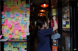 An employee removes stickers and posters with messages in support of the pro-democracy movement at a restaurant in Hong Kong,…