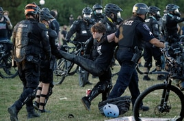 A person is arrested by Seattle Police at Cal Anderson Park, Saturday, July 25, 2020, during a Black Lives Matter protest near…