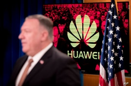 "A monitor displays the logo for ""Huawei"" behind Secretary of State Mike Pompeo as he speaks during a news conference at the…"