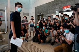 Hong Kong pro-democracy activist Joshua Wong poses with the nomination papers as he files for his candidacy in the Legislative…
