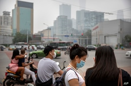 People wearing face masks to protect against the coronavirus wait to cross an intersection in Beijing, Saturday, July 11, 2020…