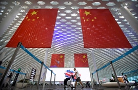 FILE - In this Oct. 10, 2018 file photo, a traveler pushes his luggage beneath large Chinese flags hanging from the ceiling in…