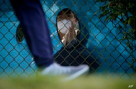 A fan wearing a face mask claps through a hole in the fence as a golfer leaves the 12h tee during the second round of the PGA…