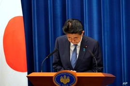 Japanese Prime Minister Shinzo Abe bows during a press conference at the prime minister official residence in Tokyo Friday, Aug…