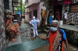 A health worker calls out to people to come out for screening for COVID-19 symptoms in Dharavi, one of Asia's biggest slums, in…