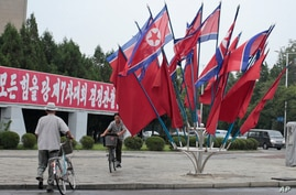"""A North Korean rides a bicycle past national flags flown to mark the celebration of the Songun Day or """"Military First"""" holiday…"""