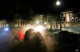 Protesters take cover from tear gas fired by police outside the Kenosha County Courthouse, late Monday, Aug. 24, 2020, in…