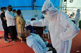 A health worker takes a nasal swab sample to test for COVID-19 at a check post erected to screen people coming from outside…