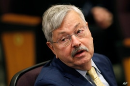 FILE - In this March 4, 2019 file photo, U.S. Ambassador to China Terry Branstad listens to Secretary of State Mike Pompeo speak at an event in Johnston, Iowa. The U.S. ambassador to China said Wednesday, April 15, 2020, that he doesn't believe…