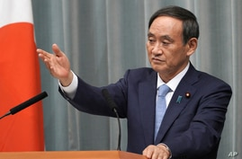 FILE - In this Sept. 11, 2019, file photo, Chief Cabinet Secretary Yoshihide Suga speaks during a press conference at the prime…