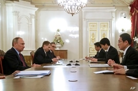 Russian President Vladimir Putin, left, meets with Japanese Foreign Minister Fumio Kishida, right, in St. Petersburg, Russia,…