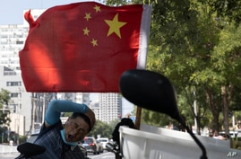 A delivery man yawns near a national flag in Beijing on Wednesday, Sept. 2, 2020. China's Ministry of Commerce on Saturday,…