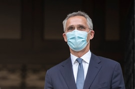 NATO Secretary-General Jens Stoltenberg, wearing a face mask stands next to Greek Prime Minister Kyriakos Mitsotakis before…
