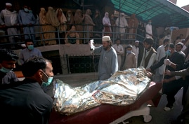 Paramedic staff transport a man wounded in a bomb explosion at an Islamic seminary to a burn ward at a hospital in Peshawar,…