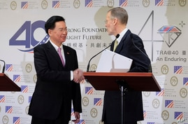 Taiwan Foreign Minister Joseph Wu, left, and American Institute in Taiwan (AIT) director William Brent Christensen shakes hands…