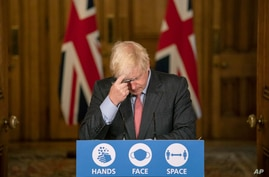 Britain's Prime Minister Boris Johnson gestures, during a coronavirus briefing in Downing Street, London,  Wednesday, Sept. 30,…