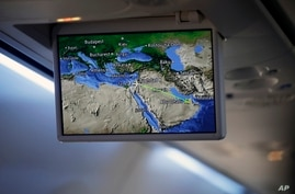FILE- In this Monday, Aug. 31, 2020 file photo, an overhead screen displays a map showing the flight route of an El Al plane…