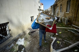 A man carries belongings from his damaged house two days after shelling by Armenian's artillery during fighting over the…