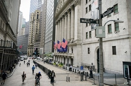 Pedestrians pass the New York Stock Exchange, Friday, Oct. 2, 2020, in New York. Stocks are pulling lower Friday, as Wall…