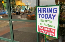 """A sign that reads """"hiring today,"""" is shown at a grocery store in Olympia, Wash., advertising a job opportunity for a meat…"""
