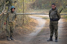 Ethnic Armenian soldiers stand at the checkpoint near the front line during a military conflict in separatist region of Nagorno…