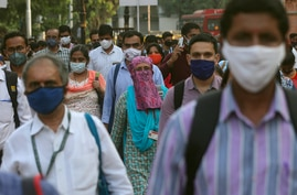 Passengers wearing masks arrive at the Chhatrapati Shivaji Maharaj train terminus in Mumbai, India, Monday, Nov. 9, 2020. India…