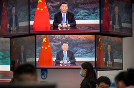 Video screens show Chinese President Xi Jinping as he delivers an address to the opening ceremony of the China International…