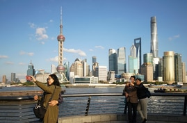 People take selfies of the Pudong skyline as they stand on the Bund in Shanghai, China, Thursday, Nov. 12, 2020. Chinese…