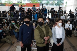 CORRECTS DATE - Hong Kong activists, from left, Joshua Wong, Ivan Lam and Agnes Chow arrive at a court in Hong Kong, Monday,…